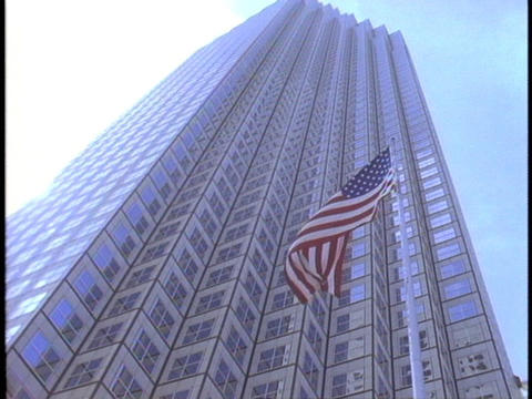An American flag waves in the wind in front of a skyscraper Footage