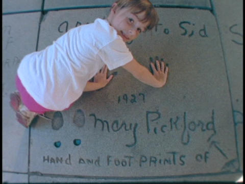 A girl puts her hands into Mary Pickford's concrete palm... Stock Video Footage