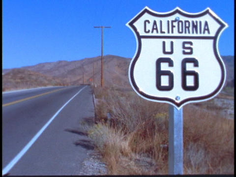 A sign along the highway reads US 66 Footage