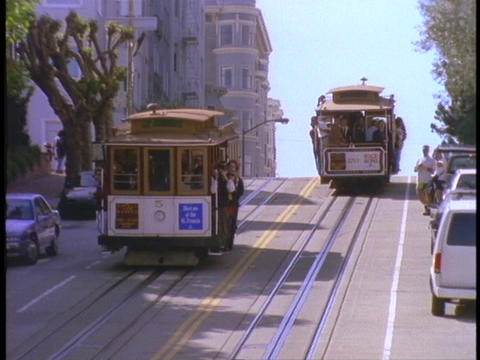 Cable cars pass on hilly San Francisco street Footage