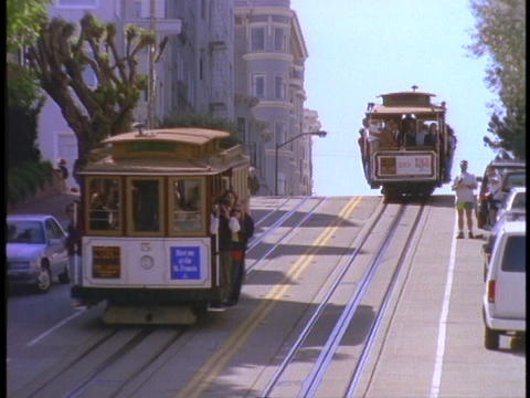 Cable cars pass on hilly San Francisco street Stock Video Footage