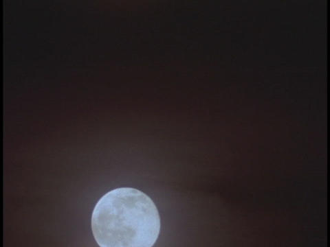 The moon rises through misty clouds Stock Video Footage