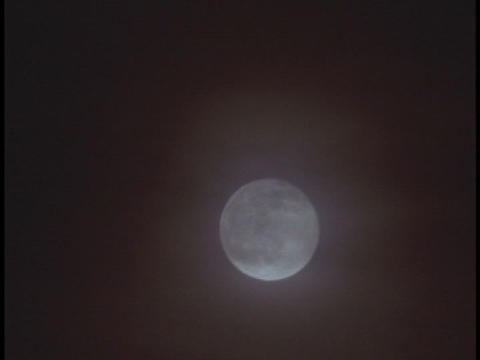 The Moon Rises Through Misty Clouds stock footage