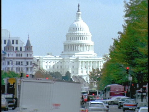 Traffic drives past the US Capitol Building Stock Video Footage