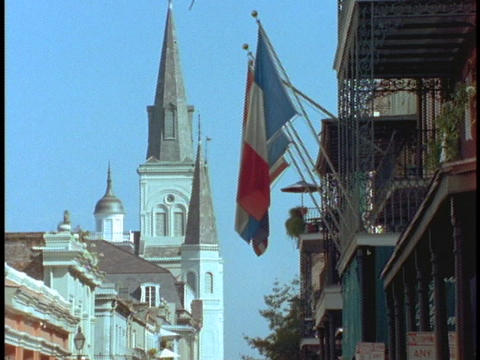 A church and French flags rise above the French Quarter Stock Video Footage