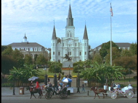 Horse drawn carriages pass in front of a church in the... Stock Video Footage