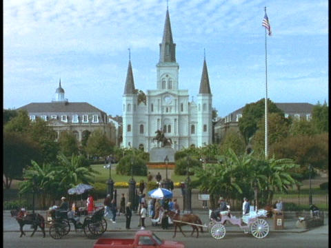 Horse drawn carriages pass in front of a church in the French Quarter of New Orleans Footage
