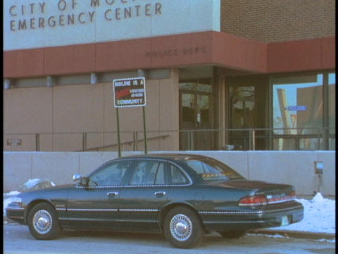 A car parks at the curb of a police station Stock Video Footage