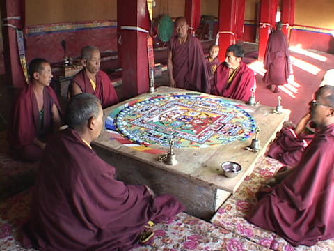 Buddhist monks sit and chant around a mandala Footage