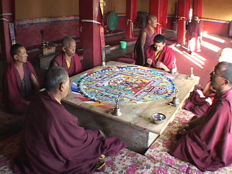 Buddhist monks sit and chant around a mandala Stock Video Footage
