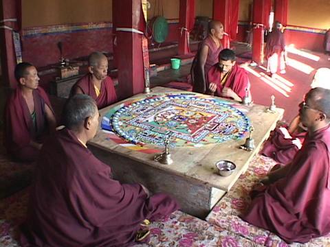 Buddhist monks sit and chant around a mandala Stock Video Footage
