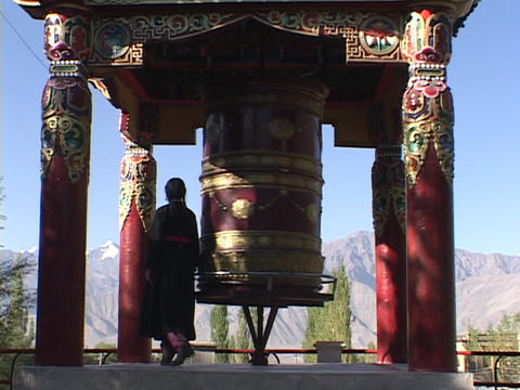 A woman spins a giant prayer wheel Footage