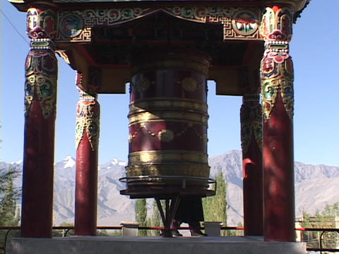 A woman spins a giant prayer wheel Stock Video Footage