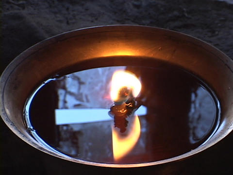 A candle burns in a small bowl Stock Video Footage
