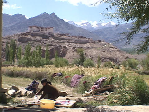 A woman washes clothes in a stream Stock Video Footage