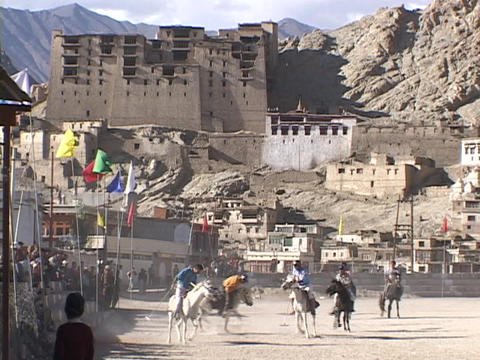 Men play polo in front of a palace in the Himalayas Stock Video Footage