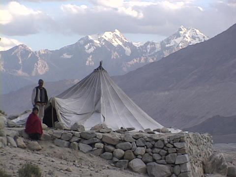A man and woman sit outside their tent in the Himalayas Stock Video Footage