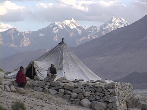 A man and woman sit outside their tent in the Himalayas Footage