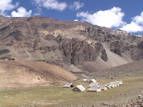 A campsite sits in a remote mountain range Live Action