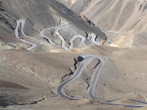A windy road curves through high mountains Stock Video Footage