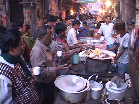 People buy food from vendors in an open air market in Calcutta, India Footage