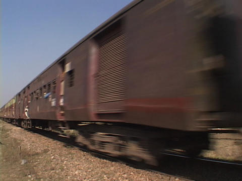 A passenger train moves along the train tracks Footage