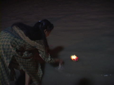 A woman puts a small aarti, floating offering, into the Ganges River at night Live Action