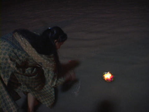 A woman puts a small aarti, floating offering, into the... Stock Video Footage