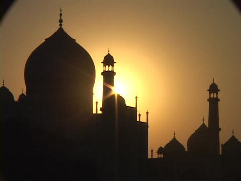 The sun silhouettes the Taj Mahal in India Footage