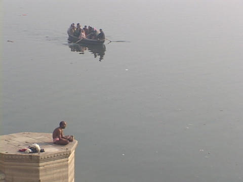 A Hindu pilgrim prays as a boat passes by on the Ganges... Stock Video Footage