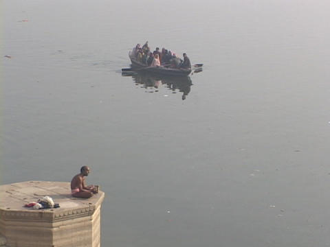 A Hindu pilgrim prays as a boat passes by on the Ganges River Footage