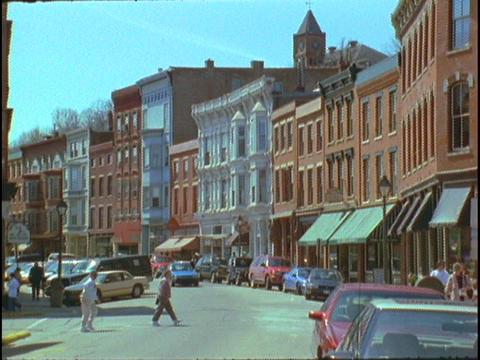 Pedestrians cross a small town main street Stock Video Footage