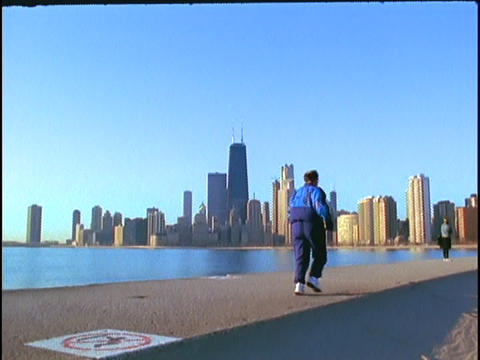 A jogger runs along Lake Michigan Stock Video Footage