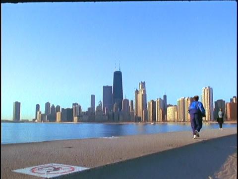 A jogger runs along Lake Michigan Stock Video Footage