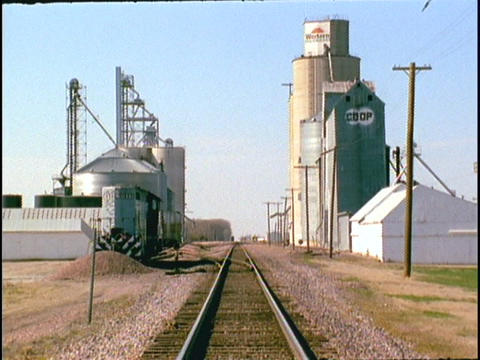 A grain silo stands along a railroad track Stock Video Footage