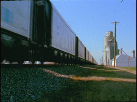 A freight train passes grain silos Stock Video Footage