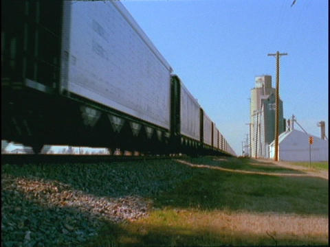 A freight train passes grain silos Footage