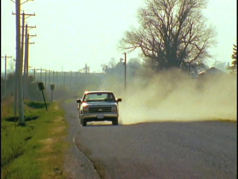 A pickup truck drives down a dirt road Footage
