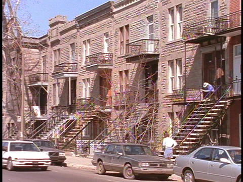 A man sits on a stoop outside an apartment building in... Stock Video Footage