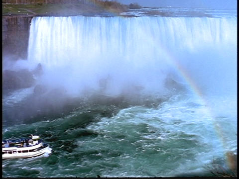 A Maid of the Mist tour boats approaches the mist of Niagara Falls Footage