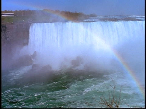 Sunlight and water mists create a rainbow on Niagara Falls Stock Video Footage
