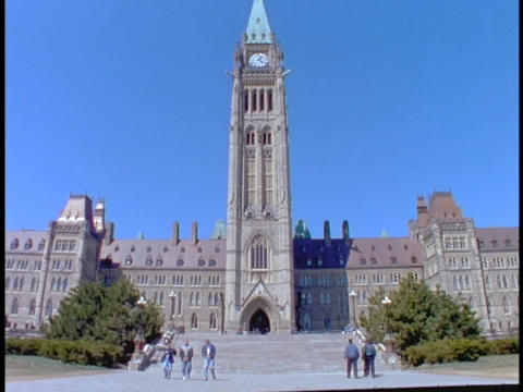 Tourists walk towards and away from Parliament of Canada Stock Video Footage