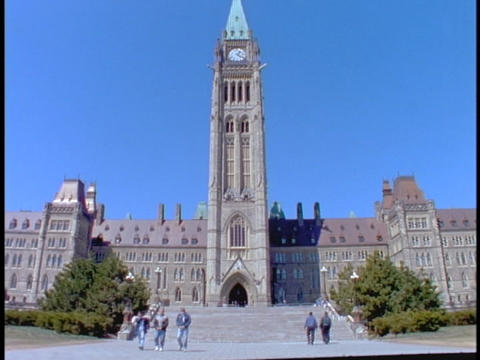 Tourists walk towards and away from Parliament of Canada Footage