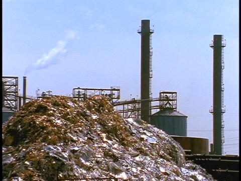 A steel waste pile sits outside large smoke stacks Footage