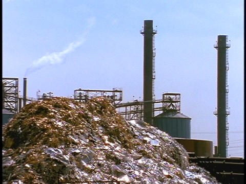 A steel waste pile sits outside large smoke stacks Stock Video Footage
