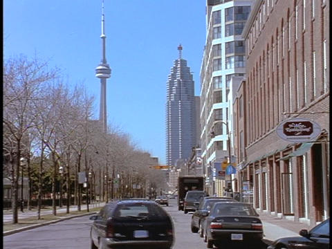 Cars drive down a street in Toronto in front of the CN Tower Stock Video Footage