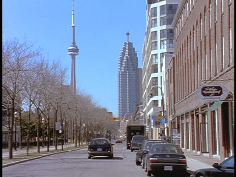 Cars drive down a street in Toronto in front of the CN Tower Archivo