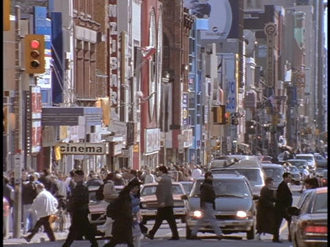 Traffic and pedestrians cross a busy intersection in... Stock Video Footage