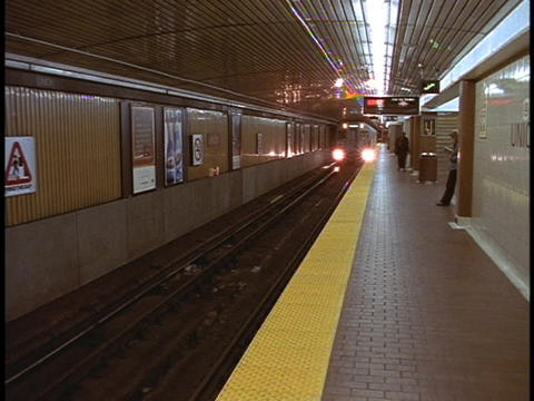 A subway train arrives at a train station Stock Video Footage
