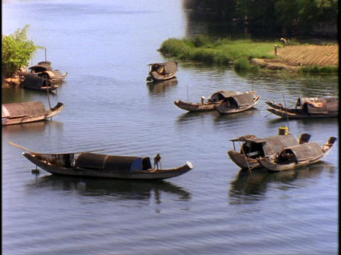 Fishing boats sit in a bay near a fishing village Stock Video Footage